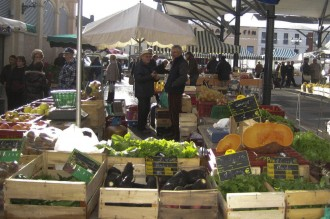 French market stall with large pumpkins